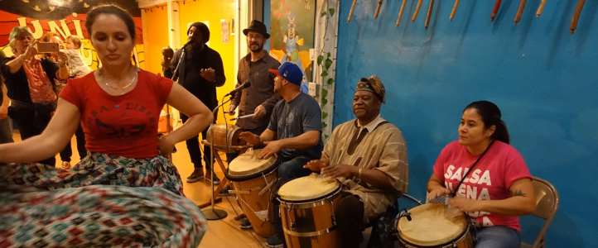 Amarilys Rios (seated, with drum), participates in a community bombazo.