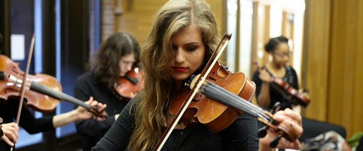 Young woman playing violin in the green room