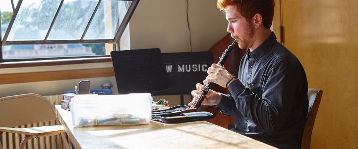 Oboist works on reedmaking.